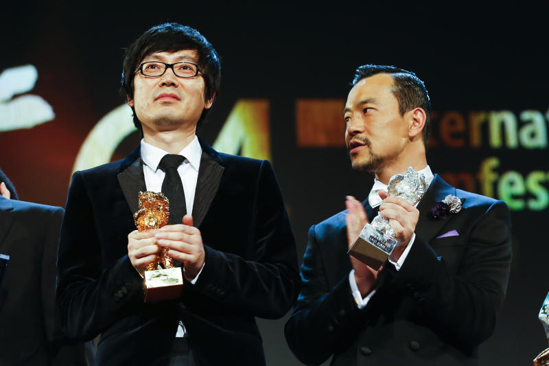 Director Diao Yinan, left, with the Golden Bear for Best Film and actor Fan Liao, right, with the Best Actor Silver Bear for the film Black Coal, Thin Ice, during the award ceremony at the International Film Festival Berlinale in Berlin, Saturday, Feb. 15, 2014. (AP Photo/Axel Schmidt)