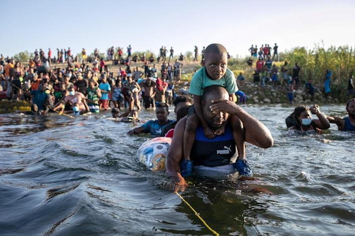 A man shields his face as he crosses the Rio Grande with a youngster on his shoulders