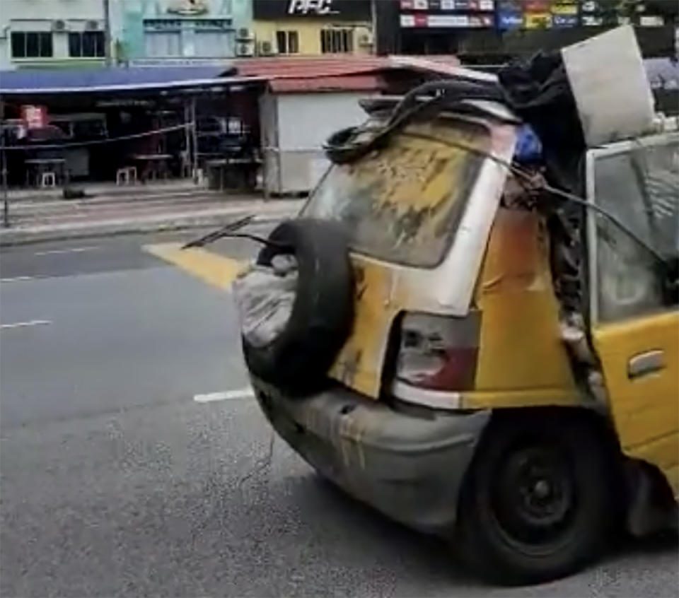 A smashed Perodua Kancil being driven in Malaysia.
