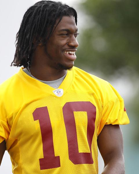 Washington Redskins quarterback Robert Griffin III walks to a morning practice at NFL football training camp at Redskins Park, Thursday, July 26, 2012, in Ashburn, Va. (AP Photo/Carolyn Kaster)
