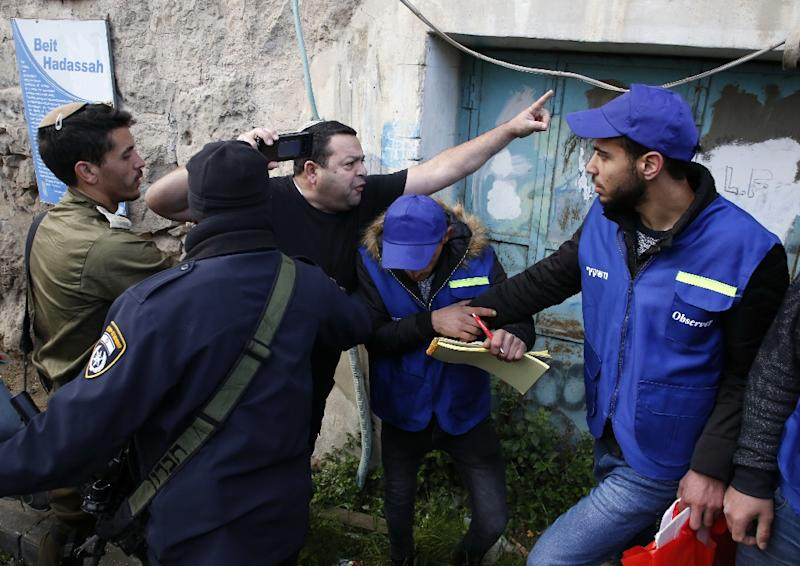 Members of the Israeli security forces intervene as a Jewish settler (C) shouts at  members of the Palestinian Youth Against Settlements (YAS) activists (R) in the occupied West Bank town of Hebron