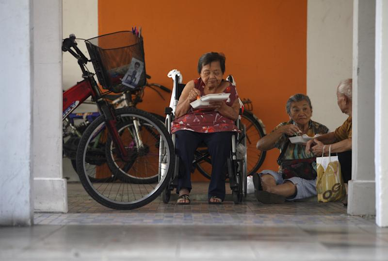 Elderly people eat their meals handed out by a charity organisation at an estate of one-room rental flats in Singapore on 22 July, 2015. (Reuters file photo)