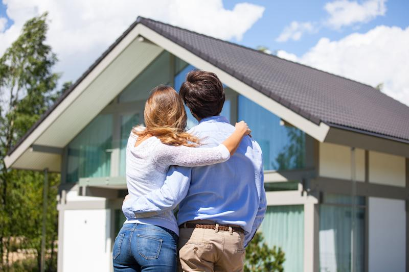 Couple looking at house with arms around one another