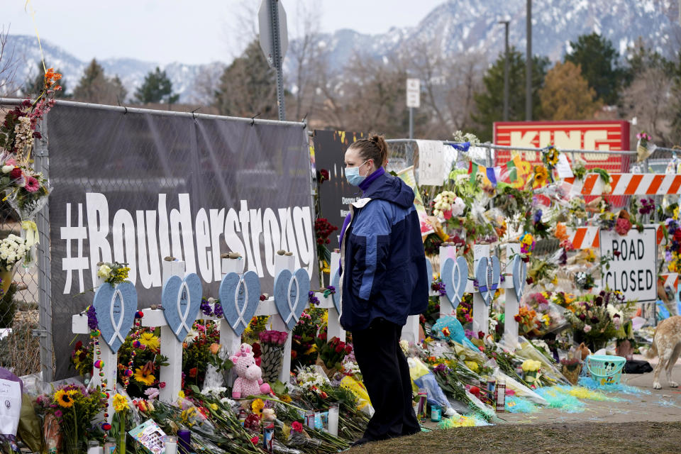 Amber Van Brocklin looks at the crosses displayed along a temporary fence set up around the parking lot of a King Soopers grocery store where a mass shooting took place earlier in the week, Thursday, March 25, 2021, in Boulder, Colo. (AP Photo/David Zalubowski)