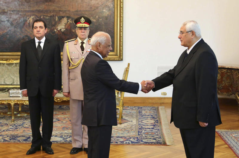 FILE - This file photo released by the Egyptian Presidency on Tuesday, July 16, 2013 shows interim President Adly Mansour, right, shaking hands with Prime Minister Hazem el-Biblawi during a swearing-in ceremony for new cabinet ministers at the presidential palace in Cairo, Egypt. Egypt's interim prime minister Hazem el-Beblawi announced Monday the resignation of his Cabinet, a surprise move that could be designed in part to pave the way for the nation's military chief to leave his defense minister's post to run for president. El-Beblawi has often been derided in the media for his perceived indecisiveness and inability to introduce effective remedies to the country's economic woes. (AP Photo/Egyptian Presidency, File)