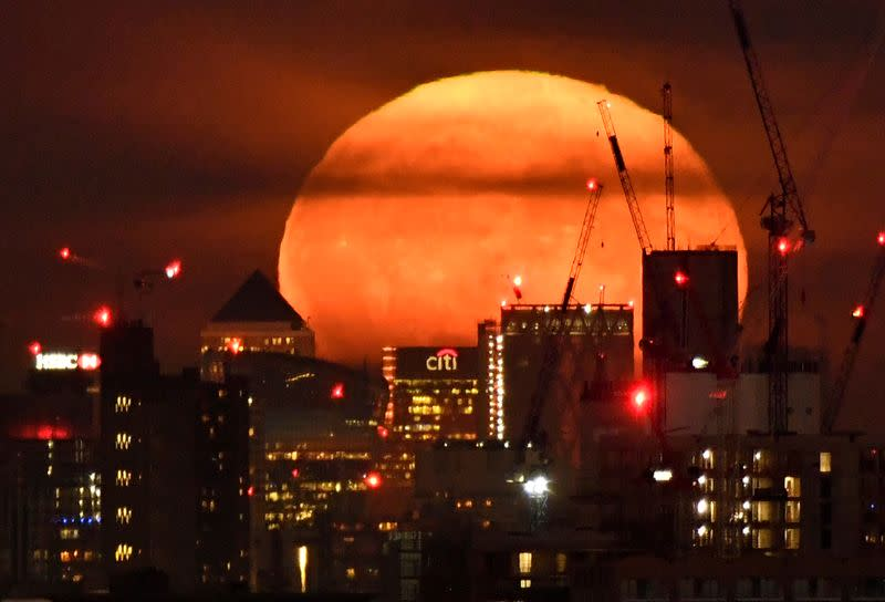 FILE PHOTO: The full moon is seen rising behind skyscrapers at Canary Wharf and the London skyline, London, Britain