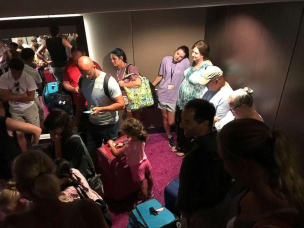 Passengers mill about the Norwegian Getaway while delayed during the search for a crew member who fell overboard on Saturday, June 30, 2018. (Bob Shellenberger)