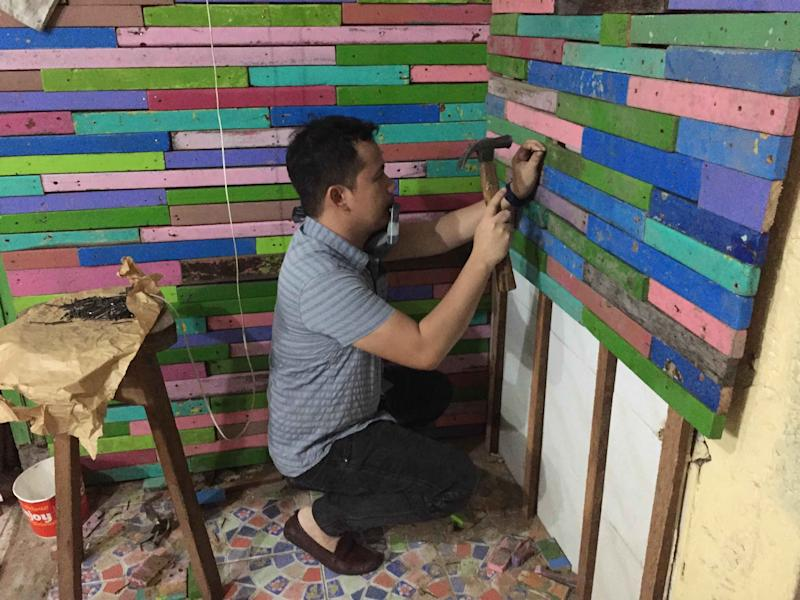 The teacher attaching the pieces of wood to the wall. (Photo: Reynel Calmerin)