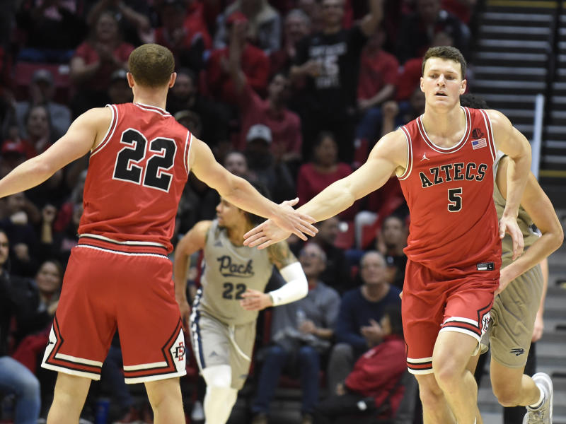 San Diego State forward Yanni Wetzell (5) slaps hands with guard Malachi Flynn (22) after scoring during the second half of an NCAA college basketball game against Nevada, Saturday, Jan. 18, 2020, in San Diego. (AP Photo/Denis Poroy)