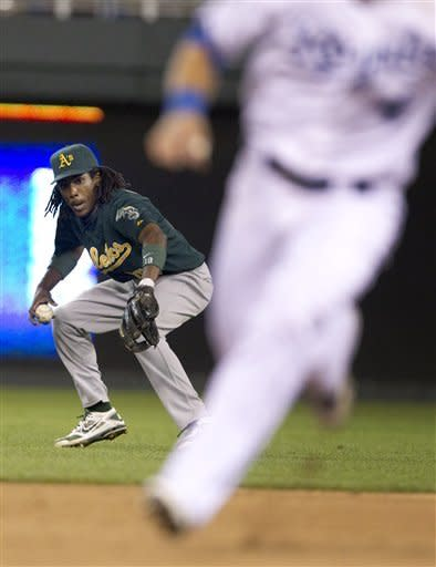 Oakland Athletics second baseman Jemile Weeks, left, looks to make a play after his error on a ball hit by Kansas City Royals' Alcides Escobar allowed Alex Gordon to advance to third base and Lorenzo Cain to score during the fifth inning of a baseball game at Kauffman Stadium in Kansas City, Mo., Tuesday, Aug. 14, 2012. (AP Photo/Orlin Wagner)