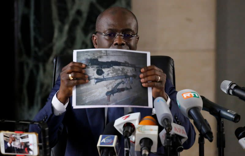 Public Prosecutor Adou Richard holds a picture during a news conference in Abidjan