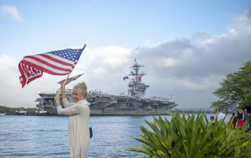A woman waves an American flag as CVN-72 arrives at Joint Base Pearl Harbor-Hickam