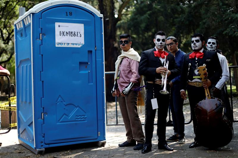 Mariachis wait to enter a bathroom before taking part in a procession to commemorate Day of the Dead in Mexico City on Saturday.