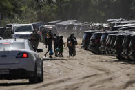 Cuban nationals, center, walk near Texas Department of Public Safety officials and vehicles on a road along the Rio Grande after crossing the river while seeking asylum, Thursday, Sept. 23, 2021, in Del Rio, Texas. (AP Photo/Julio Cortez)