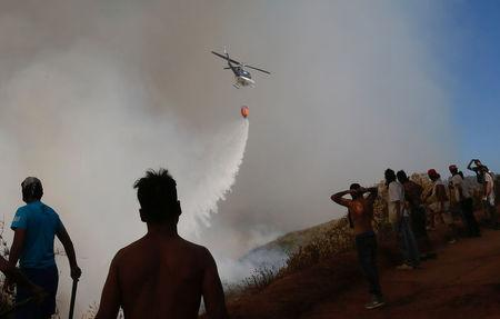 A helicopter makes a water drop to prevent a wildfire from spreading to homes in Vina del Mar