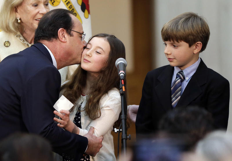 French president Francois Hollande, left, kisses a girl on the stage during a visit to city hall on Wednesday, Feb. 12, 2014, in San Francisco. Hollande is visiting San Francisco to meet politicians, lunch with Silicon Valley tech executives and inaugurate a new U.S.-French Tech Hub. (AP Photo/Marcio Jose Sanchez)