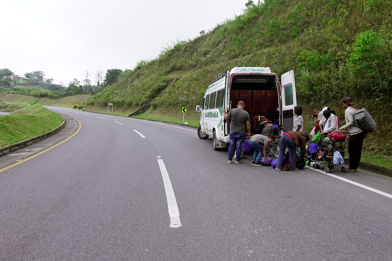 Venezuelan migrants load their belongings on a public service bus on a Colombian highway in Bucaramanga