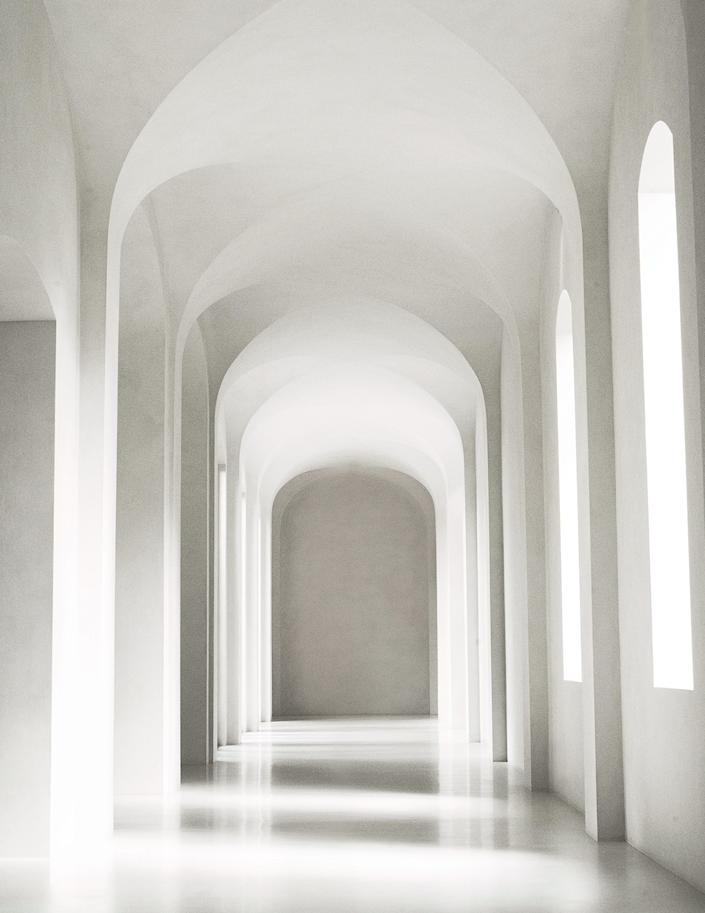 "<div class=""caption""> A soaring hallway is swathed in off-white plaster. </div>"