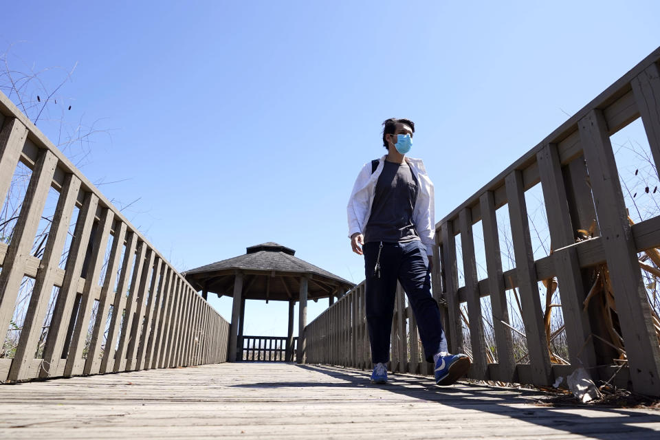 Ricardo Ramirez walks along a walkway after an interview Thursday, April 23, 2020, near his home in Houston. Ramirez is observing Ramadan for the first time as a Muslim after converting to Islam last year. Ramadan is typically a time of communal meals and praying in congregation. This year, the month comes as the coronavirus pandemic has disrupted Islamic worship and spurred mosque closures to the public. (AP Photo/David J. Phillip)