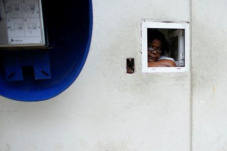 An employee peers from a window at a pharmacy in Havana, Cuba, December 1, 2017. REUTERS/Alexandre Meneghini