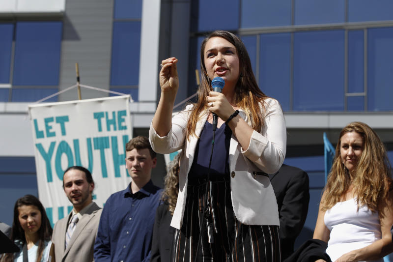 FILE - In this June 4, 2019, file photo, Kelsey Rose Juliana, of Eugene, Ore, speaks at a rally for a group of young people who filed an environmental lawsuit against the U.S. government in Portland, Ore. Oregon is on the precipice of becoming the second state after California to adopt a cap-and-trade program, a market-based approach to lowering the greenhouse gas emissions behind global warming. (AP Photo/Steve Dipaola, File)
