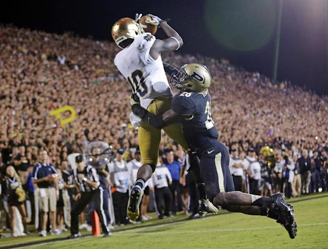 FILE - In this Sept. 14, 2013, file photo, Notre Dame wide receiver DaVaris Daniels, left, goes up over Purdue cornerback Antoine Lewis for a touchdown catch during the second half of an NCAA college football game in West Lafayette, Ind. Daniels doesn't think his 82-yard touchdown catch agaisnt Purdue was the best example of how he's improved this season. The 6-1, 200-pound wide receiver believes his 9-yard catch from Tommy Rees 2 minutes earlier was a better display of that. (AP Photo/Michael Conroy, File)