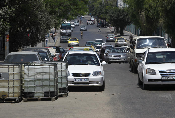 In this photo taken on Wednesday, July 31, 2013, Palestinian vehicles wait in queue to re-fuel their cars in front of gas station in Gaza City. Regime change in Egypt has cost the Hamas rulers of Gaza their most important foreign ally, and ordinary Palestinians are being caught up in the animosity. Many Gazans were laid off after Egypt closed the territory's border, and Palestinians living in Egypt are keeping a low profile for fear of being targeted in the backlash against Hamas. (AP Photo/Adel Hana)