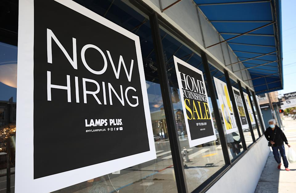 SAN FRANCISCO, CALIFORNIA - JUNE 03: A pedestrian walks by a Now Hiring sign outside of a Lamps Plus store on June 03, 2021 in San Francisco, California. According to a U.S. Labor Department report, jobless claims fell for a fifth straight week to 385,000. (Photo by Justin Sullivan/Getty Images)