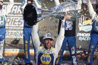 """FILE - Chase Elliott holds up the season championship trophy as he celebrates with his race crew in Victory Lane after winning the NASCAR Cup Series auto race at Phoenix Raceway in Avondale, Ariz., in this Sunday, Nov. 8, 2020, file photo. NASCAR is being heavily promoted by a broadcast partner as about to embark on """"The Best Season Ever"""" and on paper that could be true. NASCAR this year will race on dirt for the first time since 1970, the schedule includes a whopping seven road courses and five venues new to the Cup Series. Michael Jordan and Pitbull are among new team owners entering the sport in 2021 and Chase Elliott, NASCAR's most popular driver, is the reigning champion. (AP Photo/Ralph Freso, File)"""