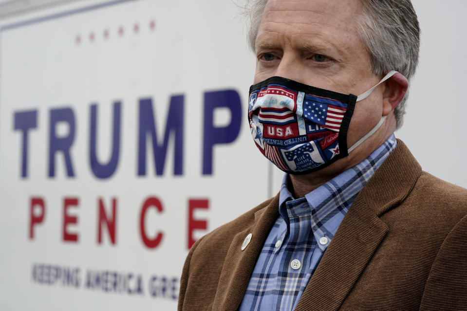 U.S. Rep. Roger Marshall, R-Kan., wearing a mask, talks to the media while attending a Concerned Women for America event outside a gun store in Kansas City, Kan. Wednesday, Oct. 21, 2020. Marshall is facing stiff competition from state Sen. Barbara Bollier in the race to fill an open Senate seat in Kansas. (AP Photo/Charlie Riedel)