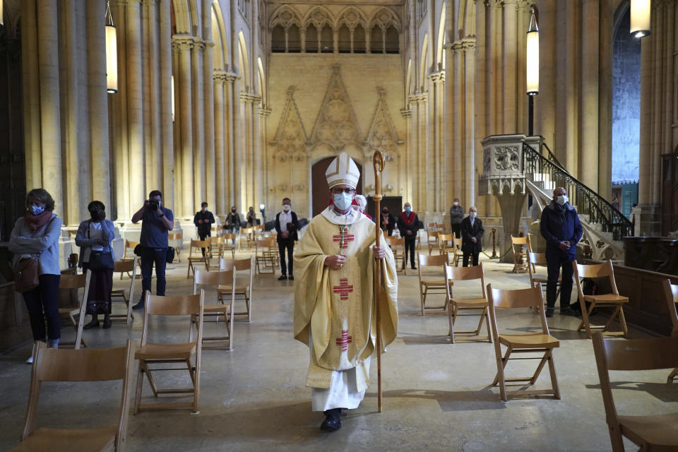 Bishop of Lyon Emmanuel Gobilliard leads mass, the first since lockdown restrictions were introduced to curb the spread of the coronavirus, at the Saint-Jean Cathedral, in Lyon, central France, Saturday, May 23, 2020. France allowed religious services to resume Saturday after a legal challenge to the government's ban on such gatherings. (AP Photo/Laurent Cipriani)