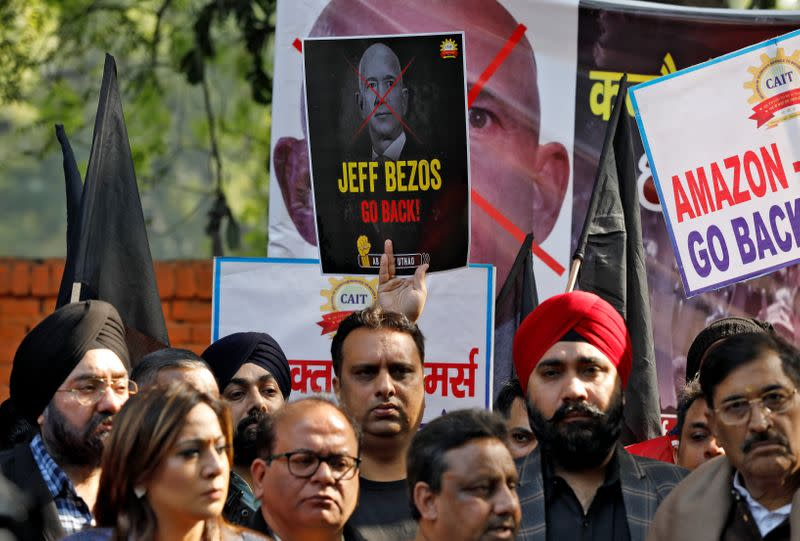 Members of the Confederation of All India Traders hold placards during a protest against the visit of Jeff Bezos to India, in New Delhi
