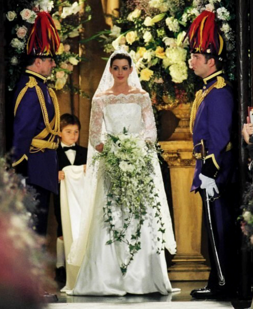 <p>As Princess of Genovia, there's no doubt that Amelia Mignonette Thermopolis Renaldi (yes, we have to say her full name) drew inspiration for her wedding gown from past royal brides. The A-line silhouette and lace sleeves give us glimmers of Grace Kelly, while the long train seems to be a nod to Princess Diana.<br></p>
