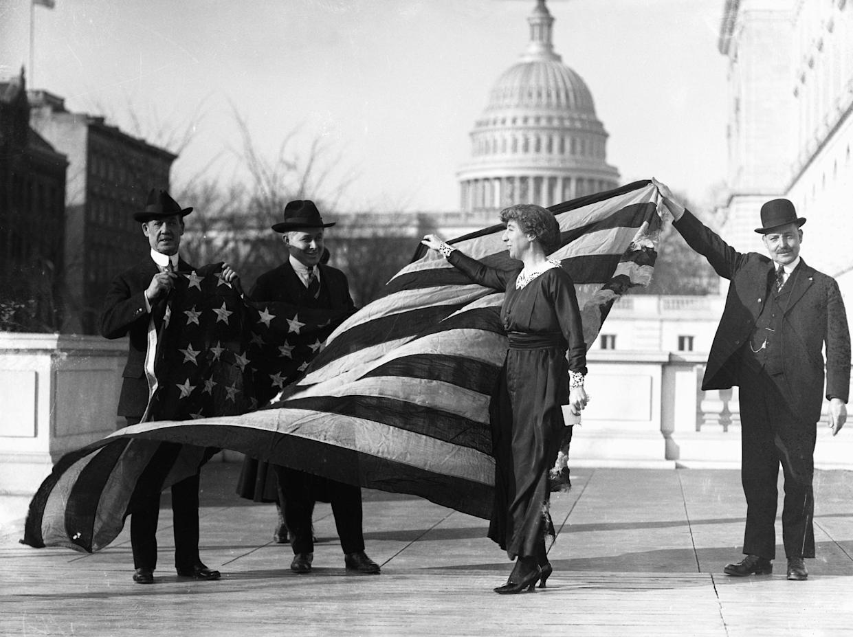 <span>Congresswoman Jeannette Rankin, center, is presented with the flag that flew at the House of Representatives during the passage of the suffrage amendment. (Photo: Bettmann/Getty Images)</span>