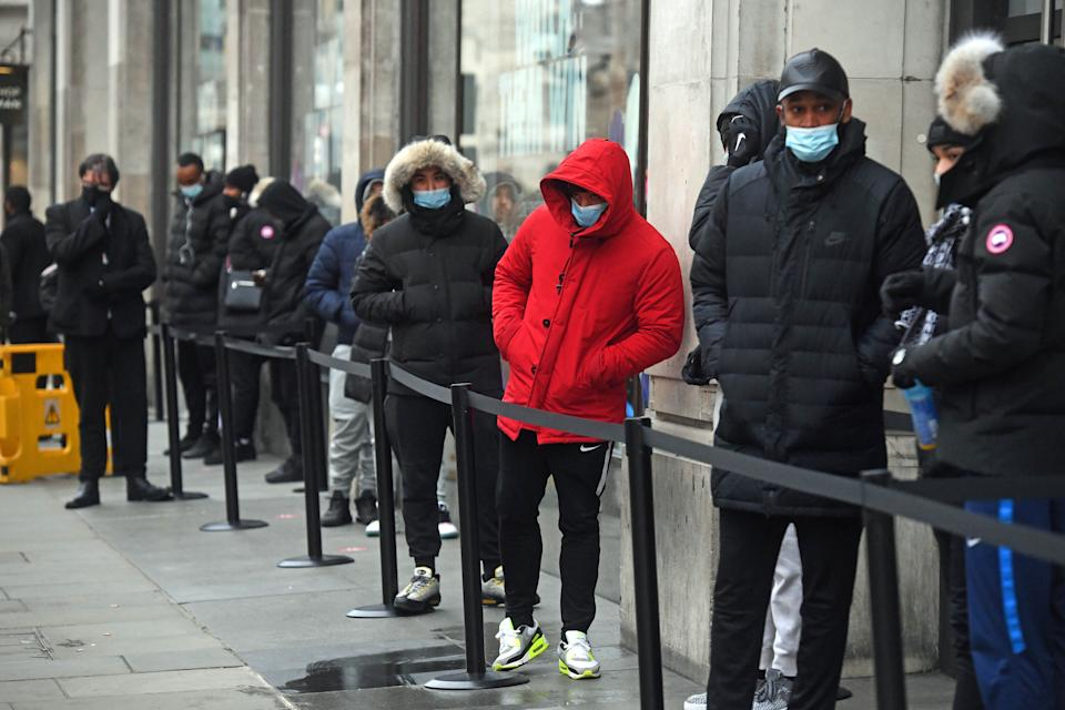 People queueing outside the Nike Town store at Oxford Circus, London, as non-essential shops in England open their doors to customers for the first time after the second national lockdown ends and England has a strengthened tiered system of regional coronavirus restrictions.