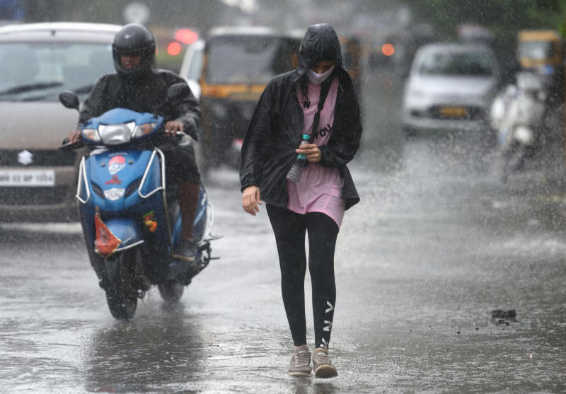 People deal with rain at Juhu, Mumbai. (Photo by Satish Bate/Hindustan Times via Getty Images)