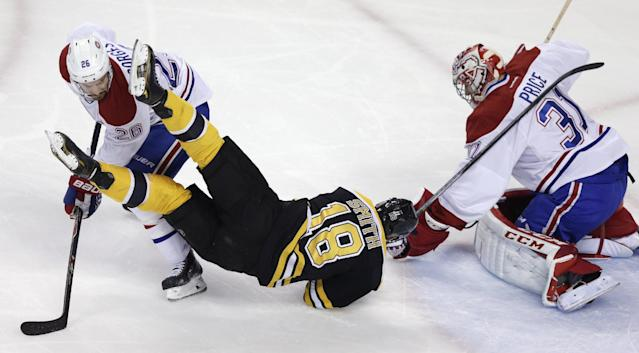 Montreal Canadiens defenseman Josh Gorges (26) upends Boston Bruins right wing Reilly Smith (18) as goalie Carey Price makes a save during the first period in Game 7 of a second-round NHL hockey Stanley Cup playoff series in Boston, Wednesday, May 14, 2014. (AP Photo)