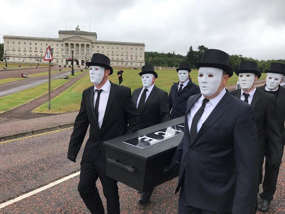 People take part in a staged funeral procession through the grounds of the Stormont estate (Jonathan McCambridge/PA) (PA Wire)