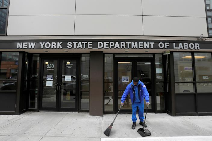A person sweeps outside the entrance of the New York State Department of Labor offices, which closed to the public due to the coronavirus disease (COVID-19) outbreak in the Brooklyn borough of New York City, U.S., March 20, 2020. REUTERS/Andrew Kelly