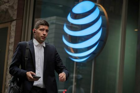 FILE PHOTO: A man uses his phone as he passes by an AT&T store on Wall St. in New York