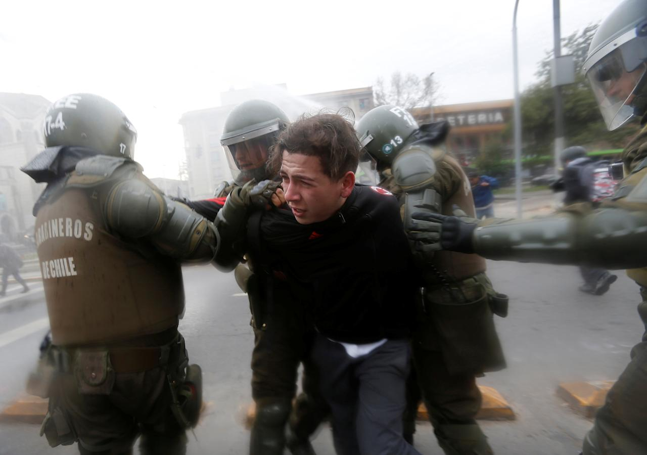 A demonstrator is detained by riot police during a protest called by students to demand improvements to the nation's higher education system in Santiago, Chile  June 21, 2017. REUTERS/Carlos Vera