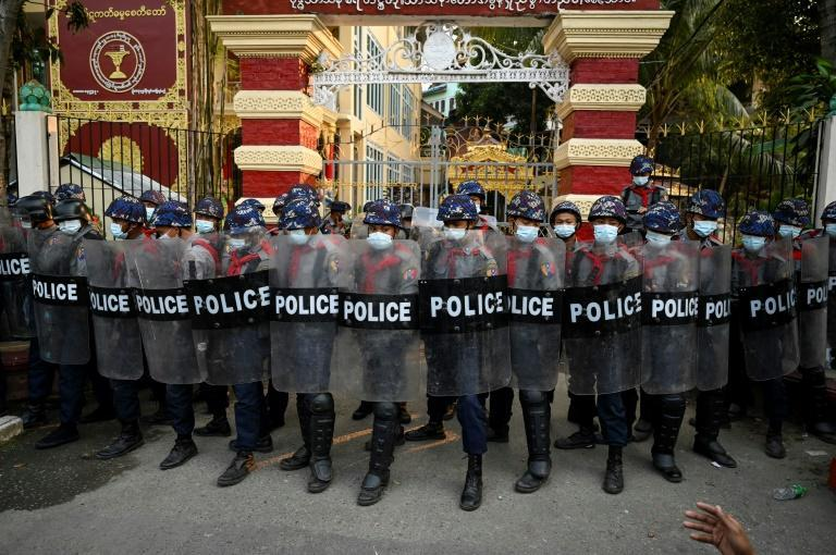 Myanmar police stand guard at the entrance gate of a Buddhist monastery where pro-military supporters took shelter after clashes in Yangon
