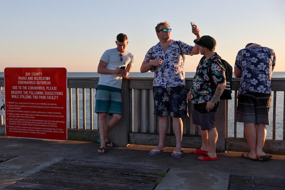Young men enjoy the view from the pier as the sun begins to set on families and spring breakers amid the coronavirus disease (COVID-19) outbreak in Panama City Beach, Florida, U.S. March 7, 2021.  REUTERS/Jonathan Ernst