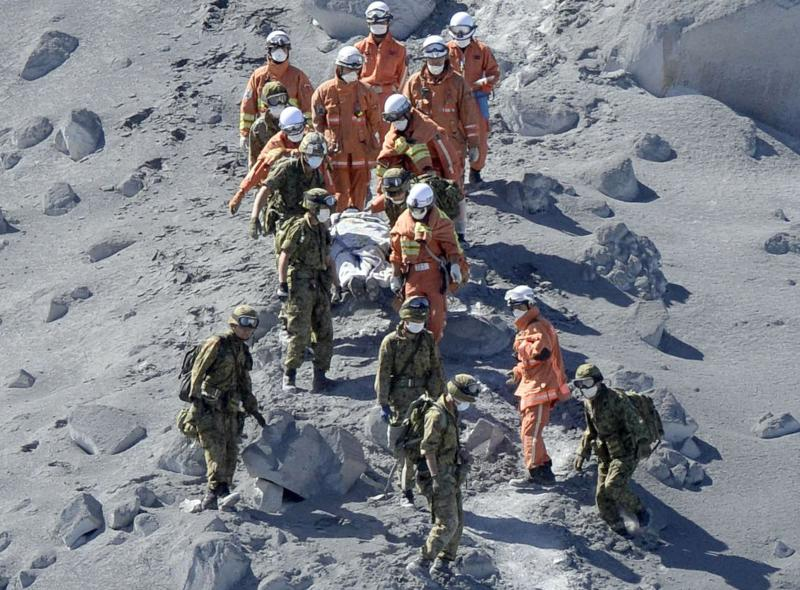 Japan Self-Defense Force (JSDF) soldiers and firefighters carry an injured person near a crater of Mt. Ontake, which straddles Nagano and Gifu prefectures in this September 28, 2014 photo taken and released by Kyodo. More than 500 Japanese military and police set out on Sunday to search the peak of a volcano popular with hikers a day after its sudden eruption trapped hundreds on the mountain for hours, amid conflicting reports about missing and injured climbers.   Mandatory credit.   REUTERS/Kyodo (JAPAN - Tags: DISASTER ENVIRONMENT SOCIETY) 