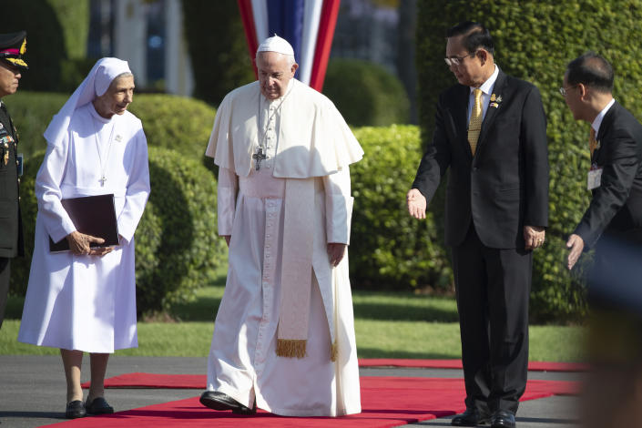 Pope Francis, center, walks with his cousin Ana Rosa Sivori, left, and Thailand's Prime Minister Prayuth Chan-ocha, second from right, during a welcome ceremony at the government house in Bangkok, Thailand, Thursday, Nov. 21, 2019. Pope Francis is on a four-day visit to Thailand. (AP Photo/Wason Wanichakorn)