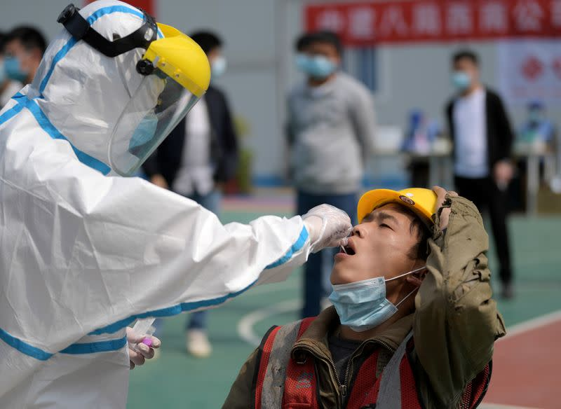 FILE PHOTO: Worker in protective suit collects a swab from a construction worker for nucleic acid test in Wuhan