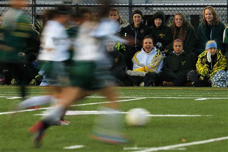 Fifteen year-old Sarah Steenhuysen (C seated) cheers on her high school soccer teammates from the sidelines during a game against Bishop Feehan in Attleboro, Massachusetts October 25, 2013. REUTERS/Brian Snyder