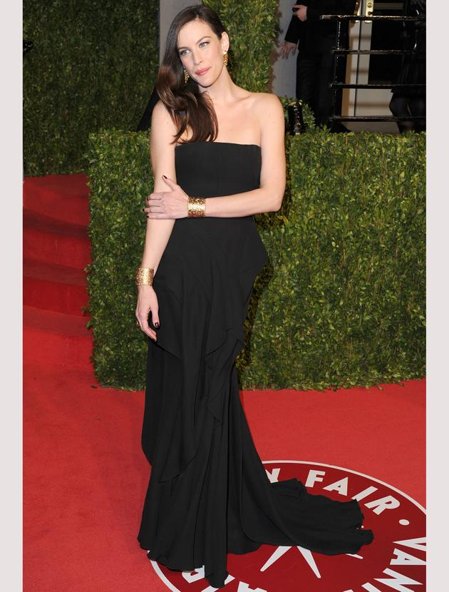 Oscars 2011 photos: Liv Tyler added interest to her black gown with gold cuffs.