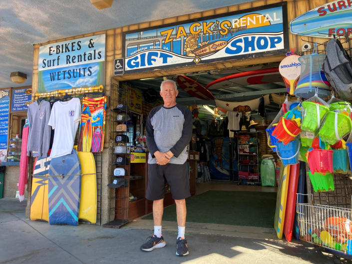Mike Ali, the owner of Zack's shop near the Huntington Beach pier, waits for customers in Huntington Beach, Calif., Sunday. Oct. 10, 2021. He says business has been hurting since an offshore pipeline leaked oil into the waters off Huntington Beach. People come in to rent bikes and food, and his business has plummeted without surf lessons and event catering. The water has been closed to surfing and swimming for a week since the spill. (AP Photo/Amy Taxin)