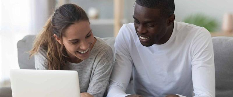 Happy mixed race young couple calculate domestic bills mortgage rates
